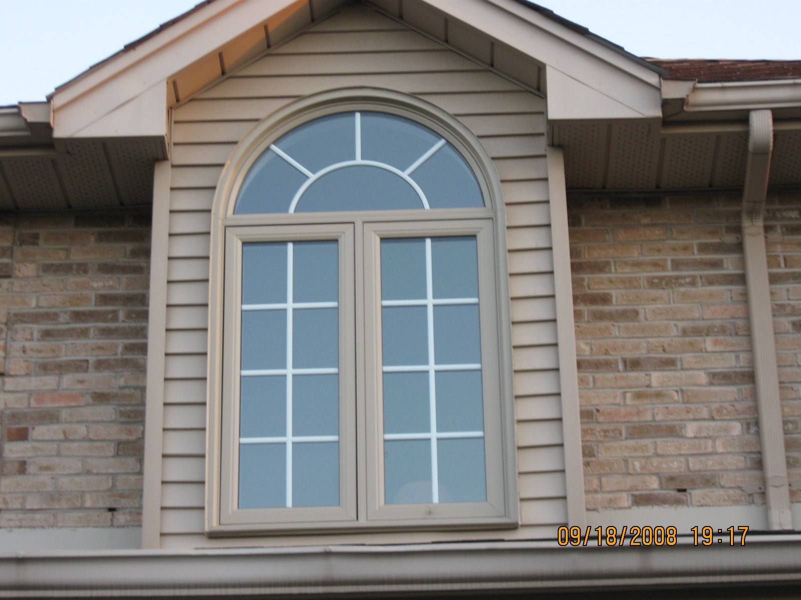 CURVED WINDOW WITH COLOURED WINDOW AND WHITE GRILLS
