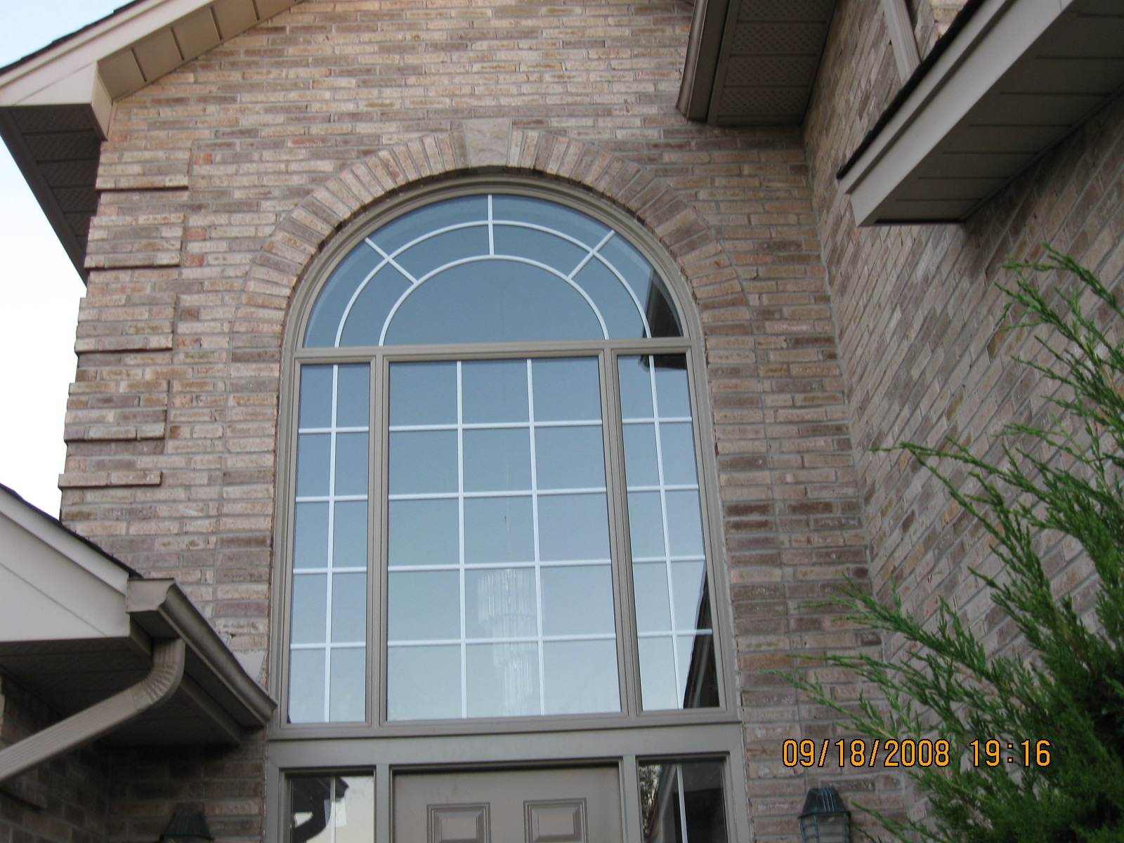 Curved window above steel door