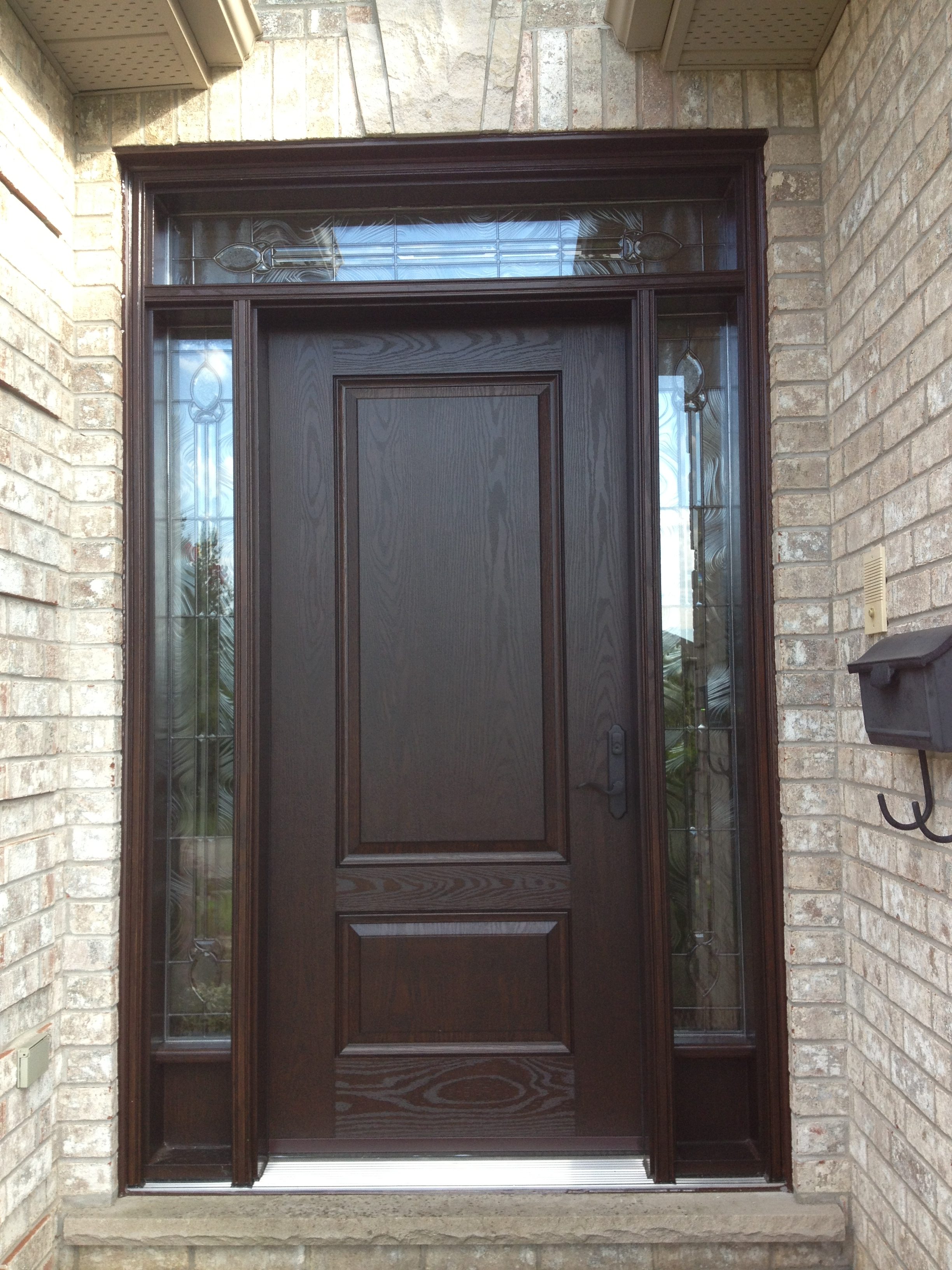 Fiberglass door with decorative sidelight glass and transom